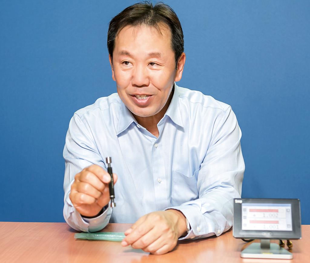 「Smp」本体のコンパクトさとカラー表示のわかり易さを説明する坂田MD。通信可能な機器も豊富でロボット等の機器への組み込みが可能になった